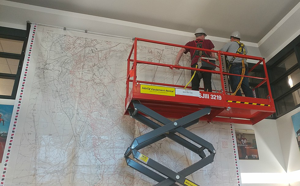 Workers install a 17ft. by 13 ft. large scale map of Vimy Ridge in the foyer of Mills Library. The map, which will be on display until November 21, was created by Canadian Geographic using trench maps from McMaster's extensive WWI collection and is available on loan to schools across Canada to help teach students about the Battle of Vimy Ridge.
