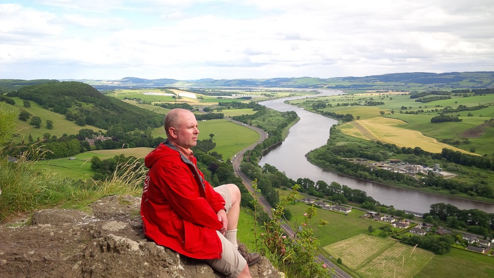 Jamie Tennant, in a red jacket, sits on a hill in Scotland
