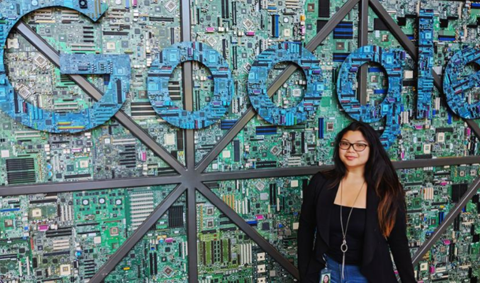 Student stands in front of Google sign