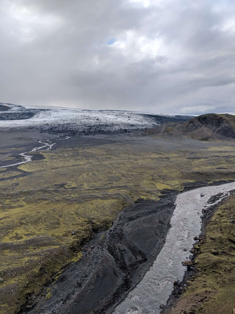 This is a picture of Öldusfellsjökull, an outlet glacier in southern Iceland. In front of the glacier a variety of glacial features can be seen: the two rivers in the image are fed by glacial meltwater (these create a variety of channelized sandy features – the black sediments on the bottom centre of the image), in the middle of the photo a variety of frontal and push moraines can also been seen (these were formed along ancient ice margins and tell us how much the glacier has retreated).