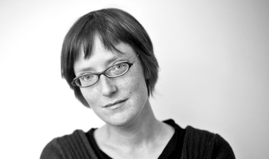 A black and white photo of a woman with short hair and glasses looking at the camera