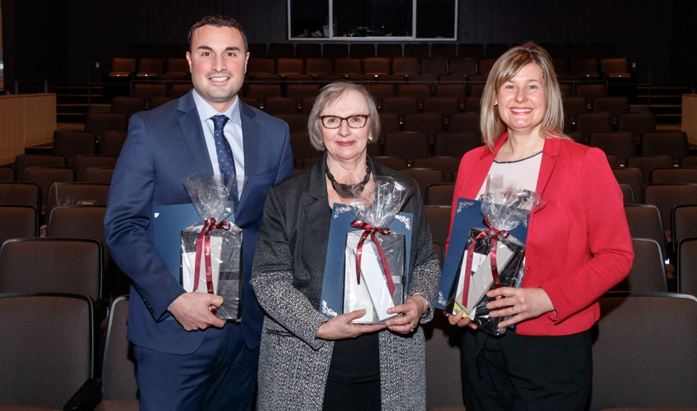 Dave Mammoliti, Sonia Hawrylyshyn and Erica Balch stand together in Wilson Hall, holding their awards