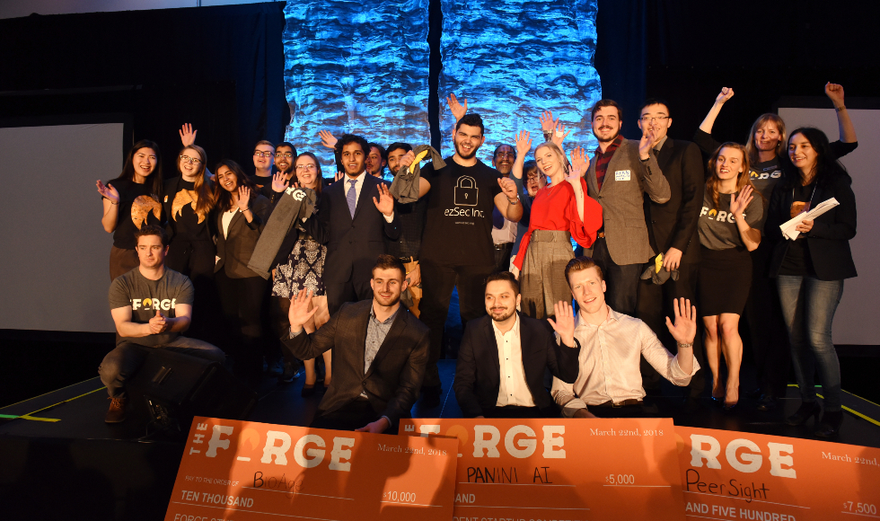 A group of students from the Forge Student Pitch Competition stand on a stage