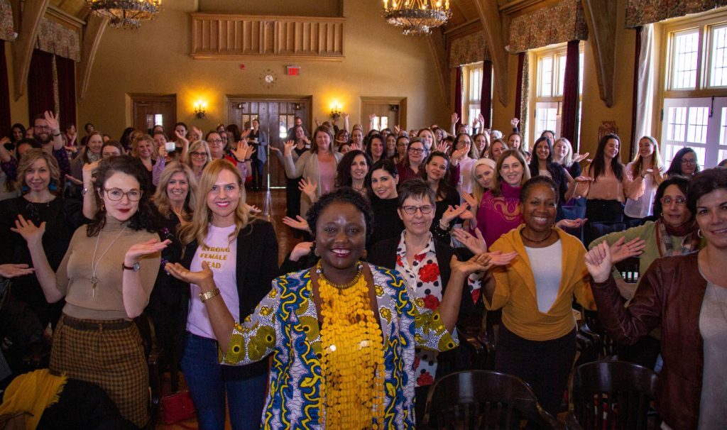 A room packed with women and a few men strike a pose with their hands up to represent