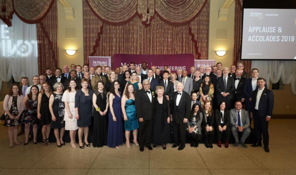Large group photo of people in front of a sign that says Applause and Accolades 2019