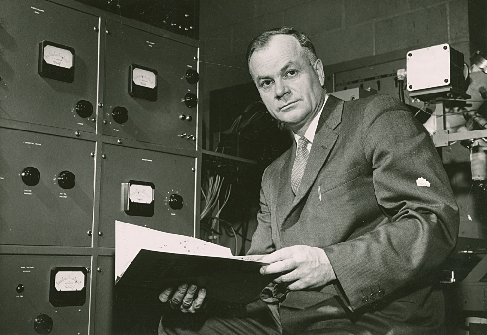 Image of Henry Those reading files in front of a filing cabinet circa 1960.