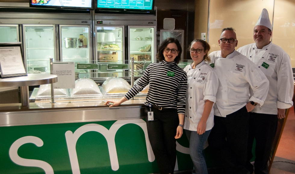 McMaster chefs stand in front of the meal counter at SMPL