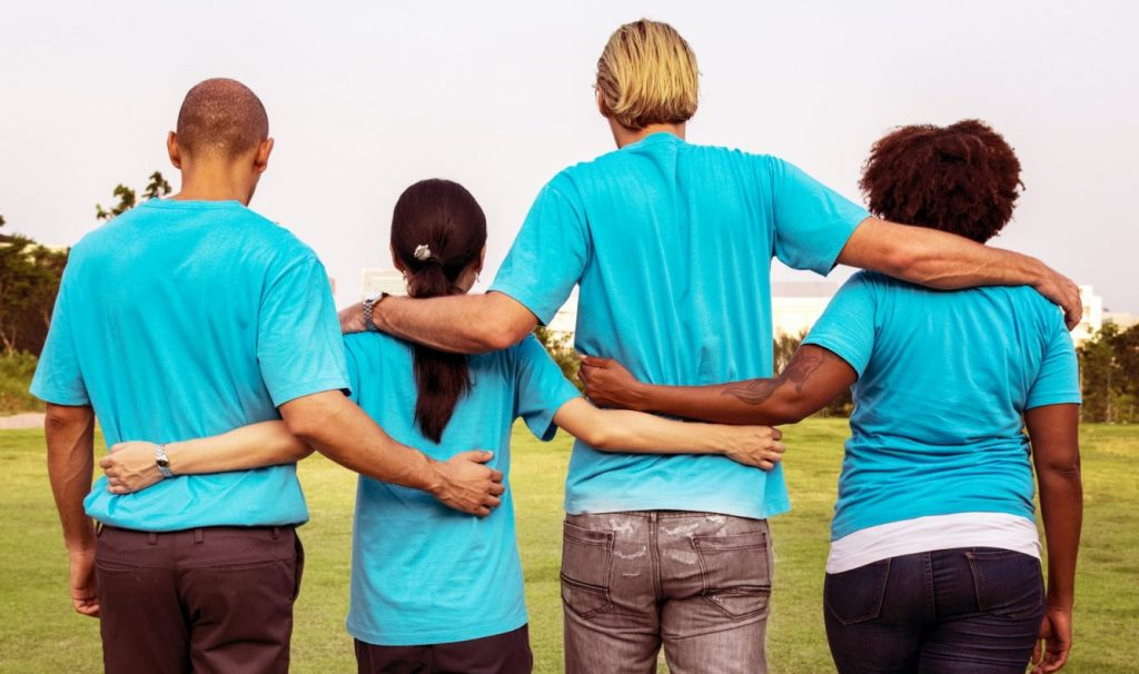Photo from behind of four people with their arms around each other's waists.