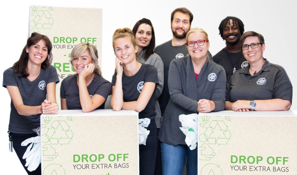 Eight Campus Store staff members stand behind boxes of reused plastic bags