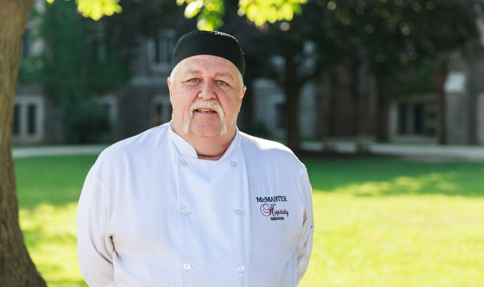 Ray Osborne stands outdoors on campus, wearing his chef uniform