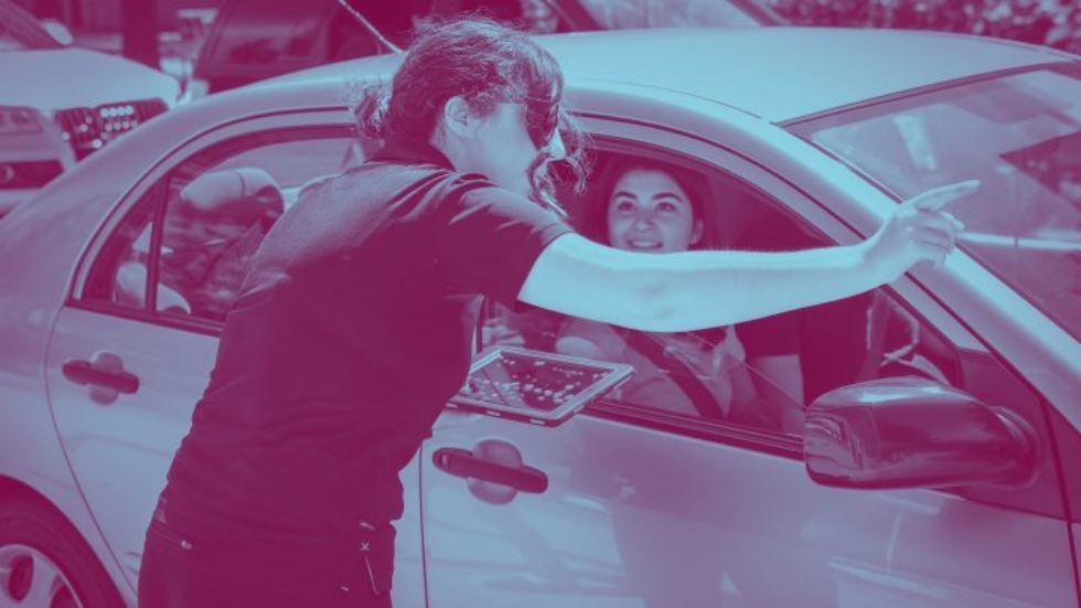 A woman directs a car with a new student moving in