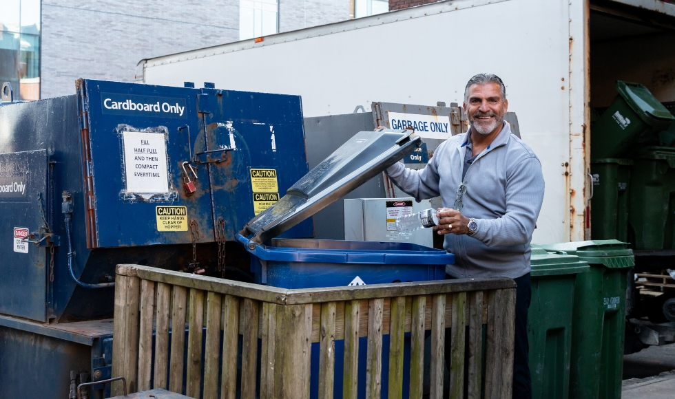 Carlos Figueira stands in front of recycling and garbage bins on campus