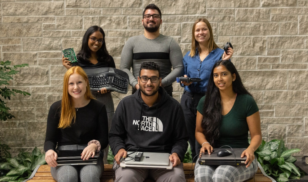 Six students hold laptops and keyboards