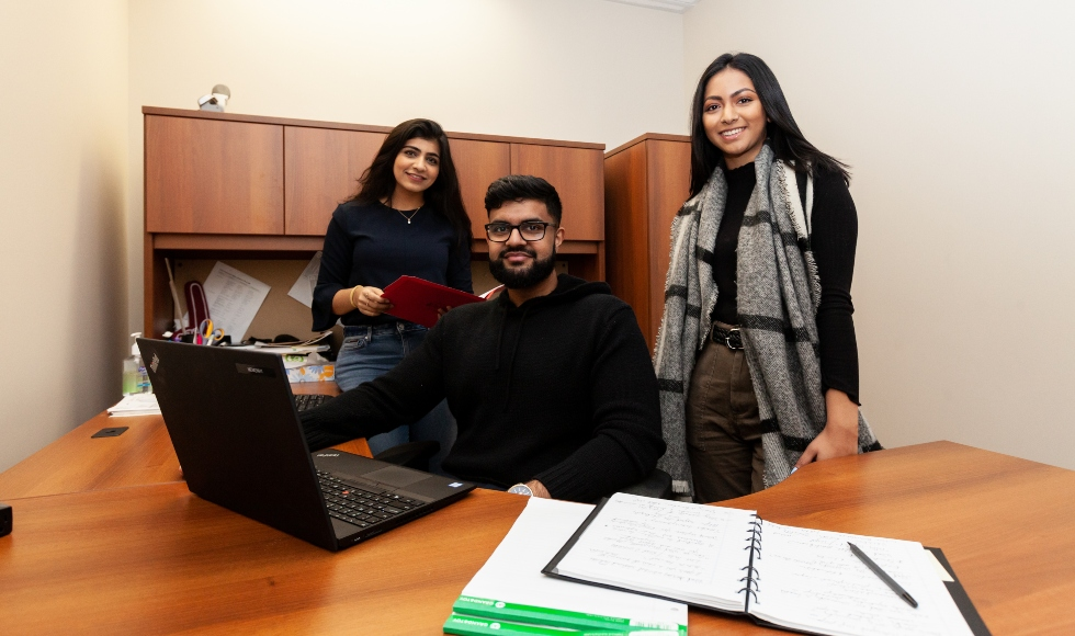 Three financial staffers pose with a laptop in a hospital office