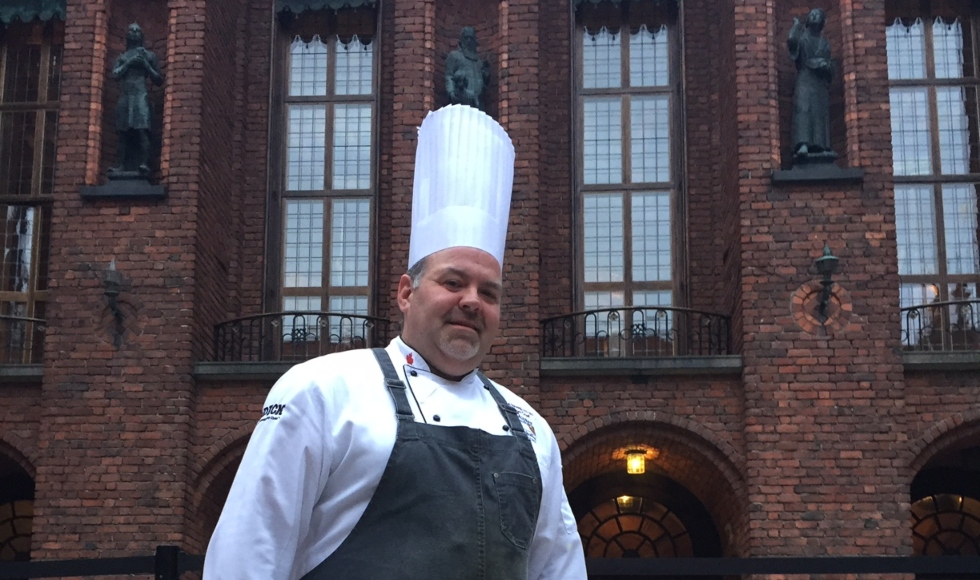 A man wearing a tall chef's hat and a black apron stands in front of Stockholm City Hall