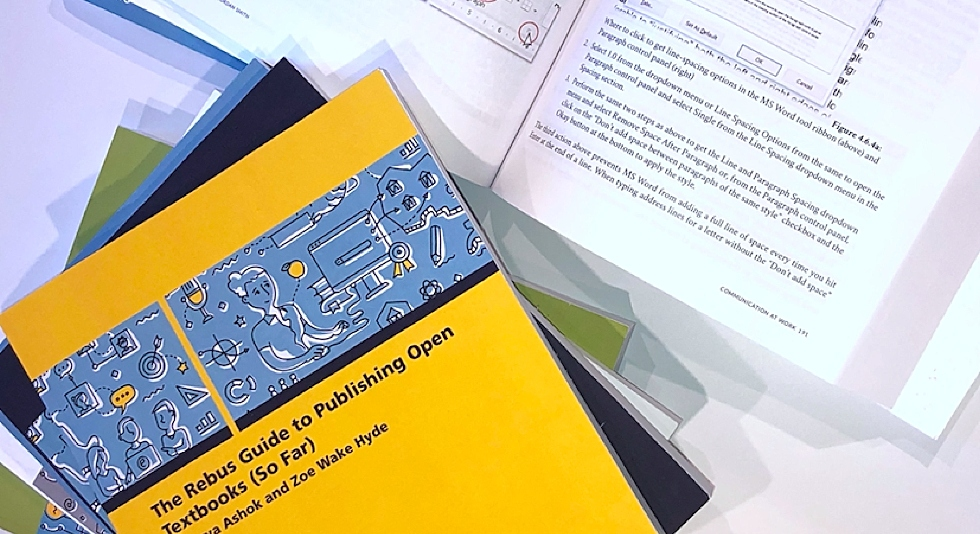 Image of open text books laid out on a table.