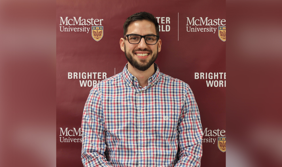 head and shoulders of Matt Horner, smiling against a wall with McMaster logo on it.