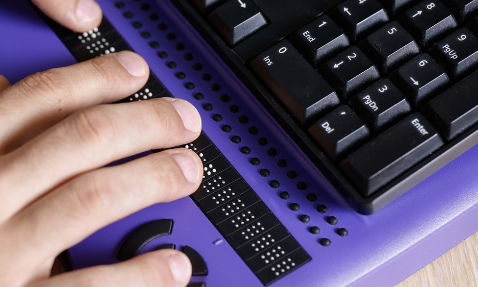 close up Image showing someone typing using braille on a purple keyboard. Only the person's right hand is visible.