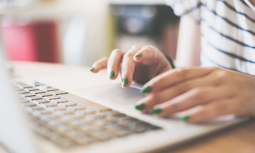 Stock image of a female student with green nail polishing working at her laptop