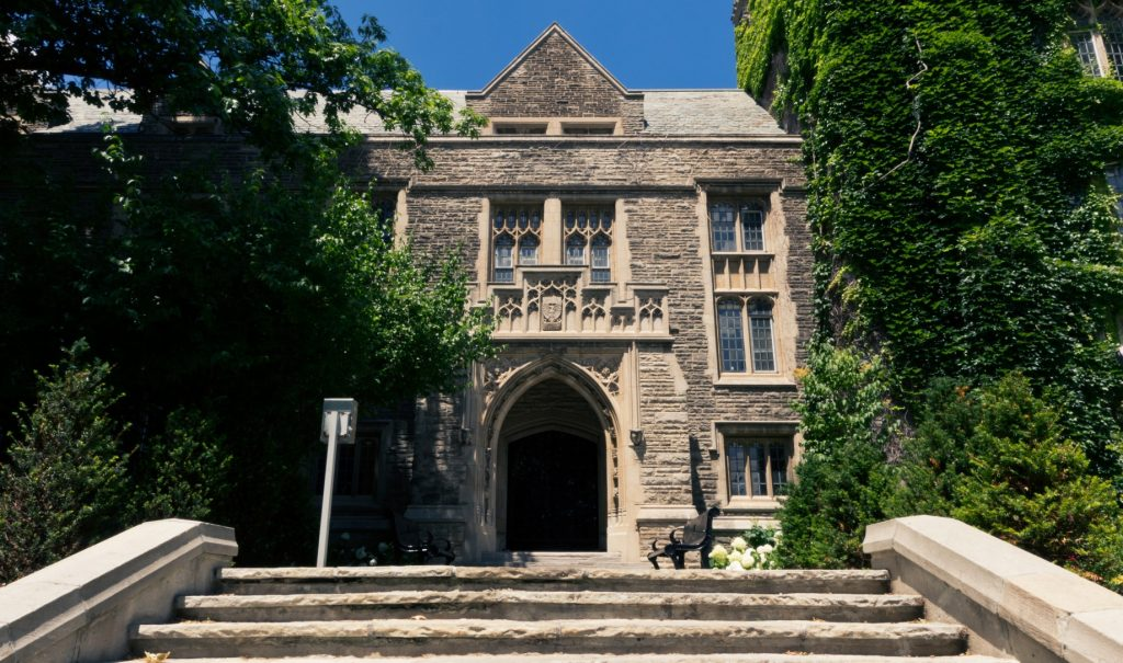 University Hall in the daytime, a big beautiful grey stone arched doorway covered in vines.