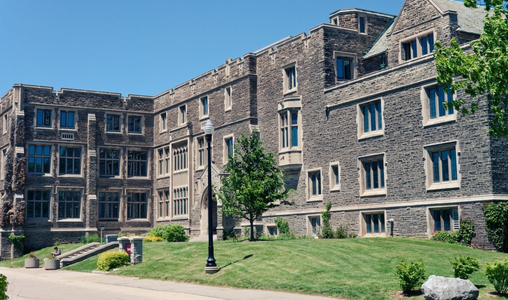 External shot of Hamilton Hall on a sunny day. It's a grey stone building. No people in this picture.
