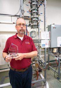 A man in a red shirt holding a glass award stands in a lab