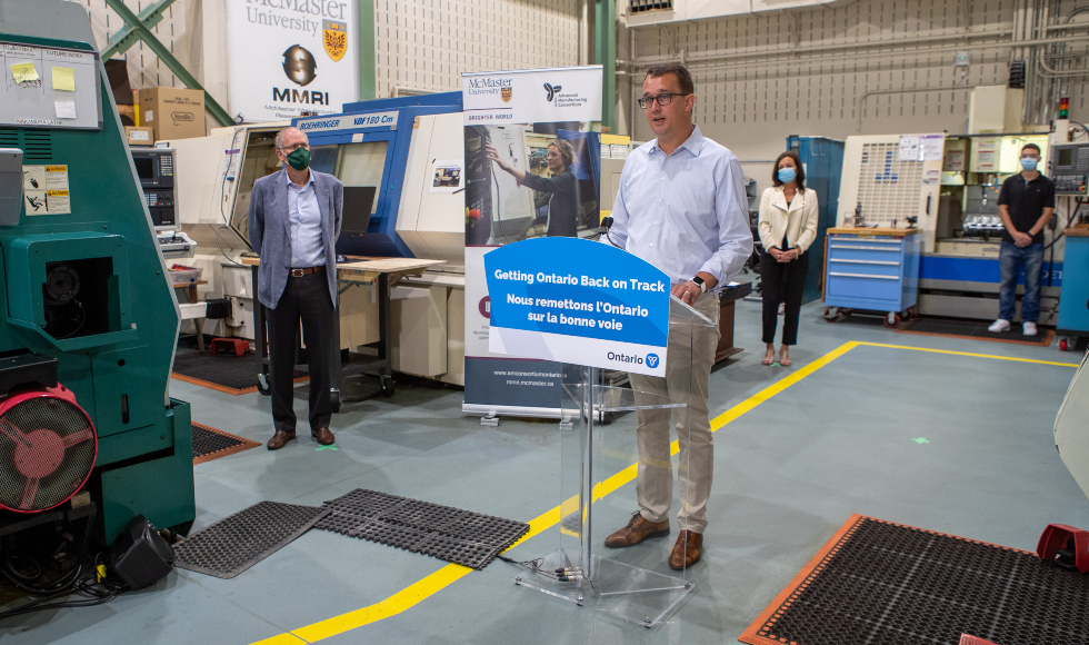 Minister Monte McNaughton stands at a posium in the McMaster Manufacturing Research Institute. President David Farrar and MPP Donna Skelly are in the background.