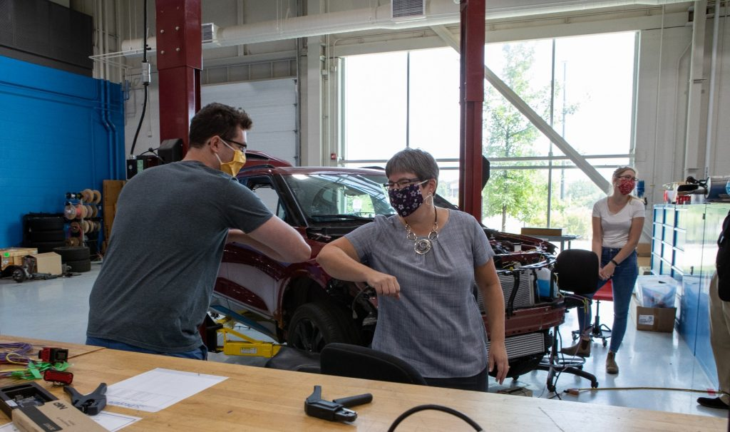 Two people wearing masks bump elbows in a workshop. Behind them is a car with its hood popped open, lots of machinery and tools everywhere.