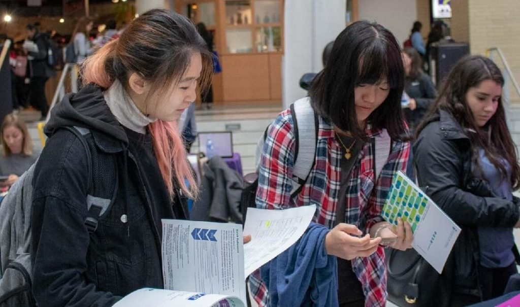 Three women, who look like students, are looking down at handouts and brochures in McMaster's Student Centre.