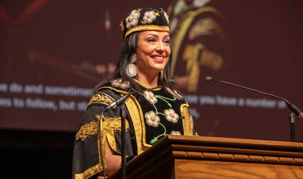 A woman in beaded robes stands at a lectern