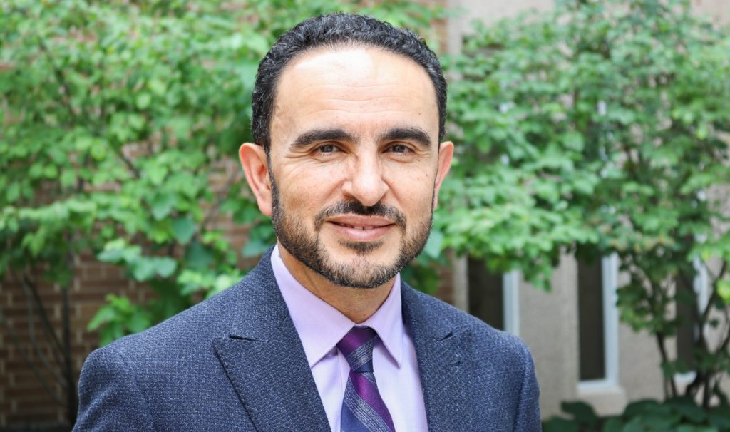 Head and shoulders of Khaled Hassanein, wearing a suit and tie and smiling into the camera.