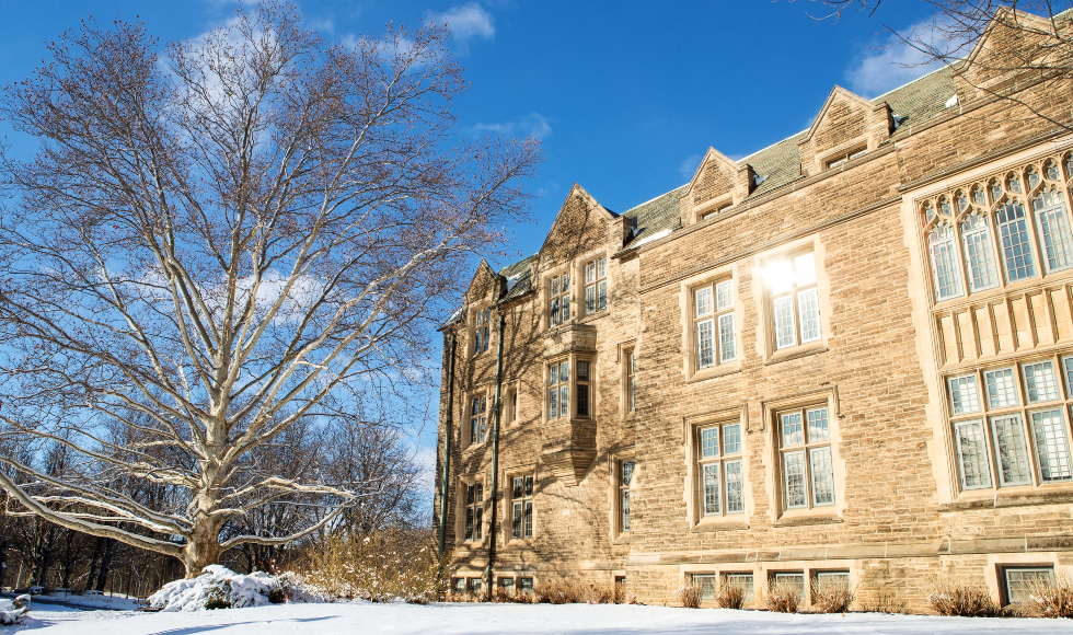 A photo of UNiversity Hall in winter with a bright blue sky and sunshine