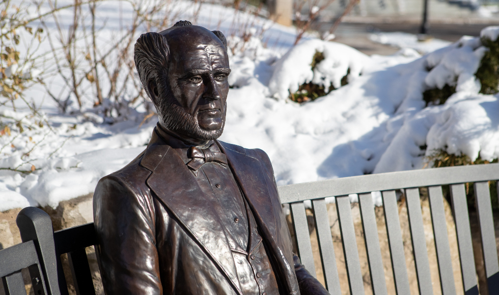 A metal statue of Senator William McMaster sitting on a metal bench in the snow