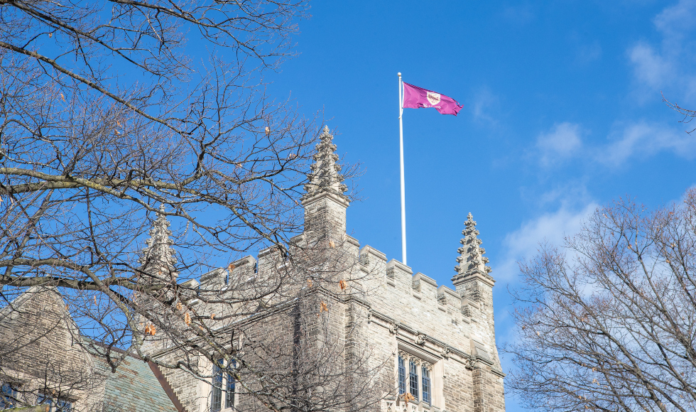 THe McMaster flag, flying on top of UNiversity Hall against a blue sky