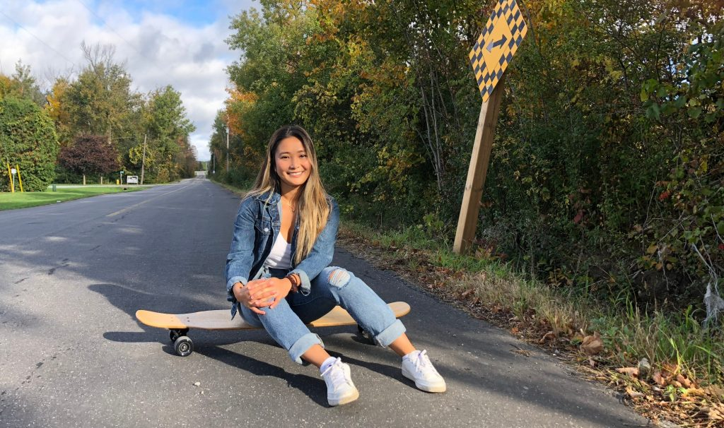 Kaitin Jingco sitting on a skateboard on an open road, smiling at the camera
