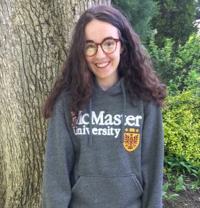 A smiling girl with long hair and glasses wearing a McMaster sweatshirt