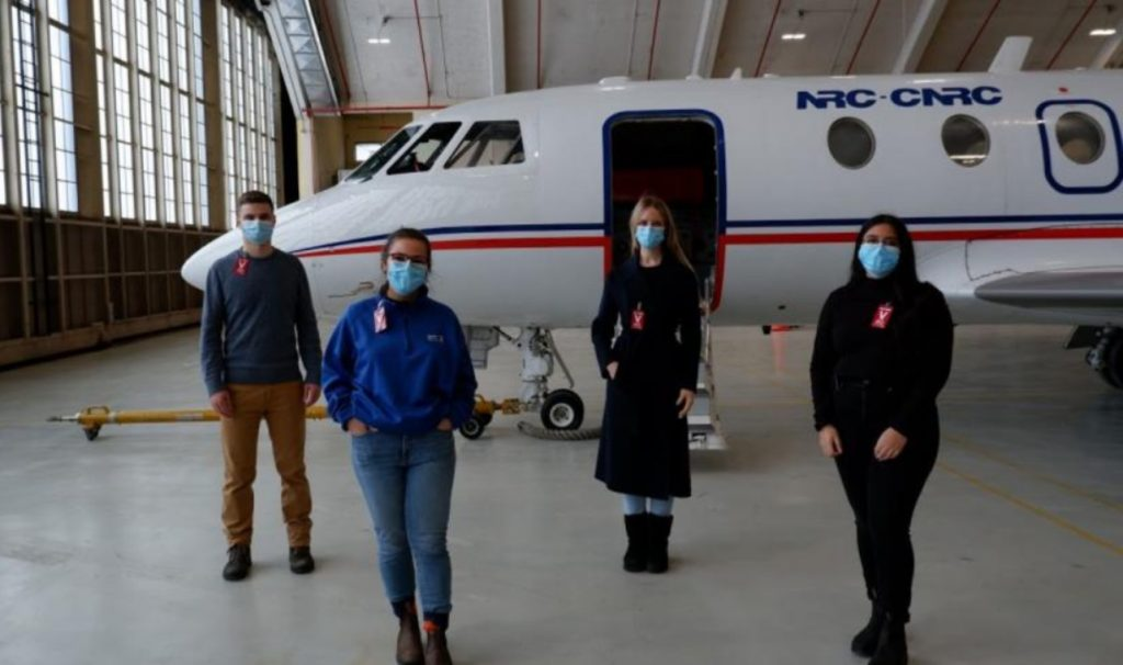Four students wearing masks and standing distanced in front of an airplane in a hangar.