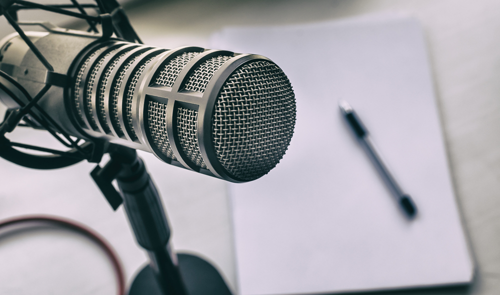 A photo of a microphone sitting on a desk, with a pad of paper and a pen