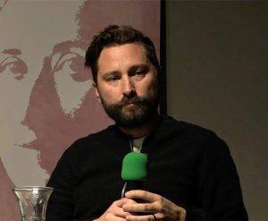 A bearded man talks into a microphone with a green foam head
