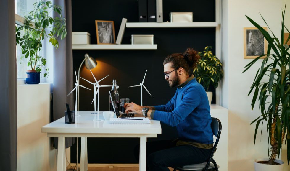 Profile shot of a bearded man sitting at a desk, working on a laptop. There are wind turbines outside the window behind him.