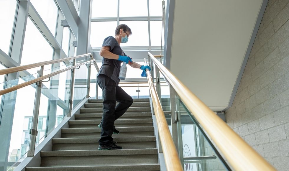University employee cleans a staircase on campus.