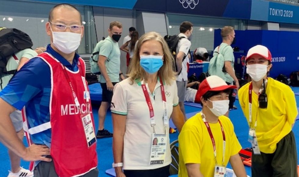 4 masked people in Olympic-branded clothes at an aquatic centre.