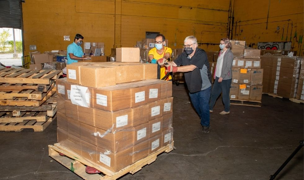 4 people, two of whom are pushing a pallet loaded with cardboard boxes.